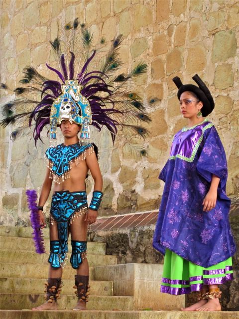 Man and woman in stylized Aztec costume in jewel tones.