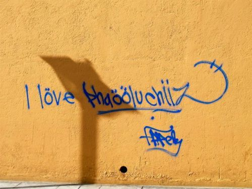 "Shadow on wall that looks like a podium; words written ""I love Phaooluchiiz. Signed by Fapely"""
