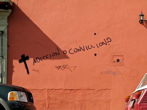"Painted on wall: a cross followed by words ""adiccion o conviccion?"""