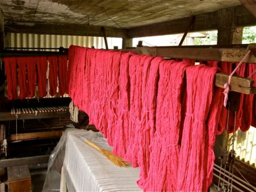 Hanks of pinkish/red yarn hanging above looms