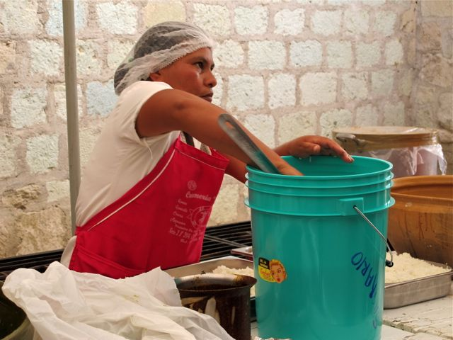 Woman in apron and wearing hairnet, scoops cooked rice out of a large bucket.