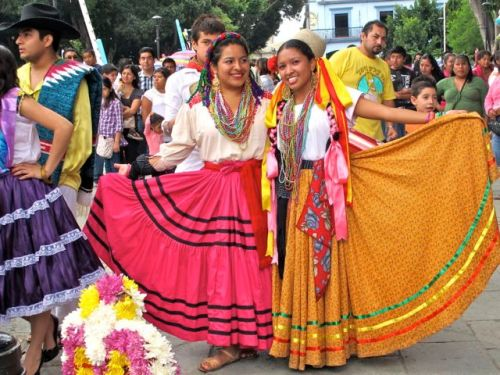 Two women displaying their long  colorful full skirts
