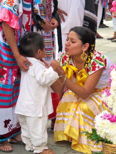 Woman squatting down and clasping hands with a toddler-age boy - both in indigenous dress