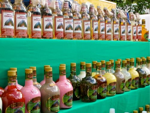 Bottles of mezcal lined up in two shelves of a display