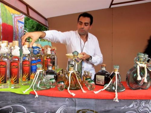 Male vendor reaching for a bottle of mezcal