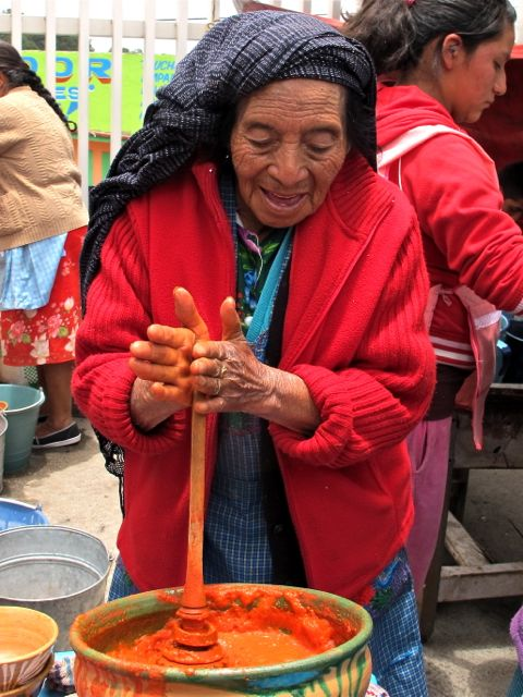 Elderly woman mixing atole rojo.