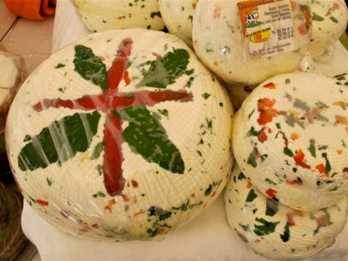 Ball of cheese decorated with basil leaves and red bell pepper strips.
