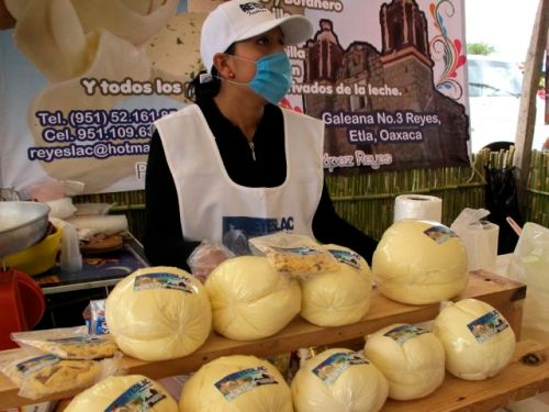 Woman vendor wearing mask behind display of quesillo