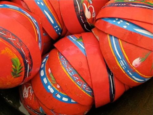 Dried and hollowed-out gourds painted red with blue, yellow, and green decoration.