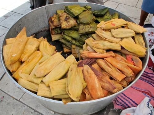 Large galvanized aluminum bucket filled with a variety of tamales wrapped in corn husks and banana leaves.s