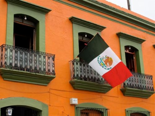 Mexican flag hanging from second floor of building.