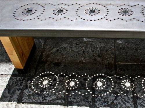 Bench with metal seat with punched design, which is mirrored in the shadow on the paving stones.