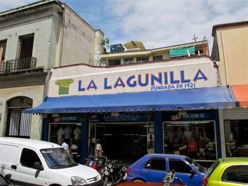 Cars in front of one story white building with blue awning and name, La Lagunilla, painted at the top of the building