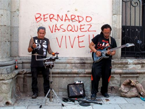 2 street musicians; one wearing a U2 t-shirt and other a Motley Crue t-shirt