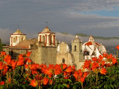 Glowing red/orange African tulip tree blossoms in foreground, church domes and bell towers in background against, tops of mountains in distance, against blue sky with bands of fog.