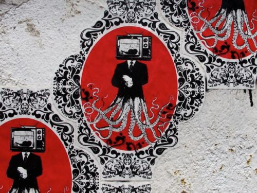 Close up of sticker of a person with a monitor for a head and tentacles for legs, on front of building