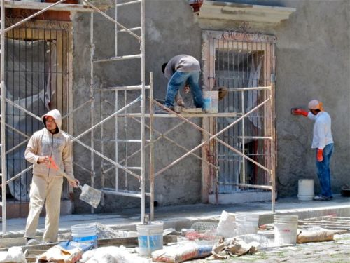 Guy mixing cement with shovel, guy on scaffold, and another standing on sidewalk plastering wall