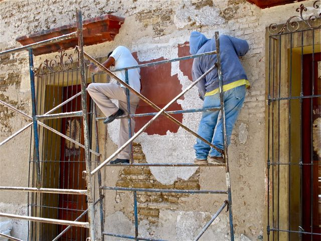 Two guys on scaffold chipping away plaster from face of building