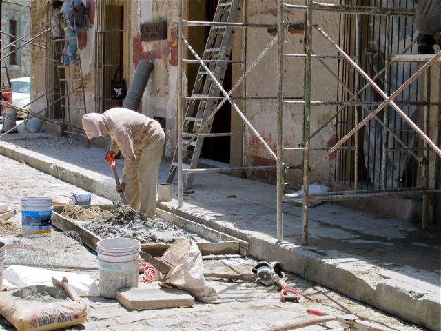 Guy mixing cement with a shovel in front of scaffolding