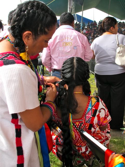 Woman standing braiding a hair extension into a seated woman's hair.