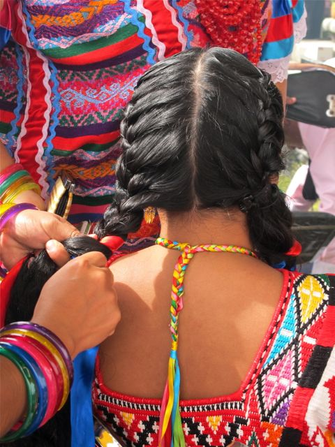 Close-up of hands braiding ribbons into hair