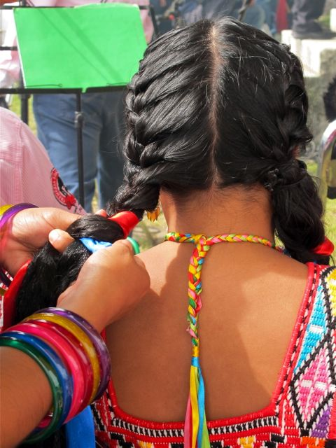 Hands braiding ribbons into hair.