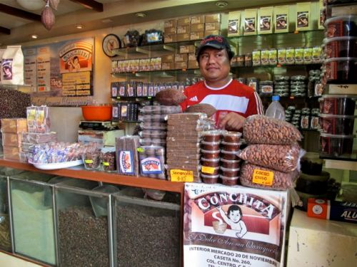 Male sales clerk behind counter filled with chocolate products.