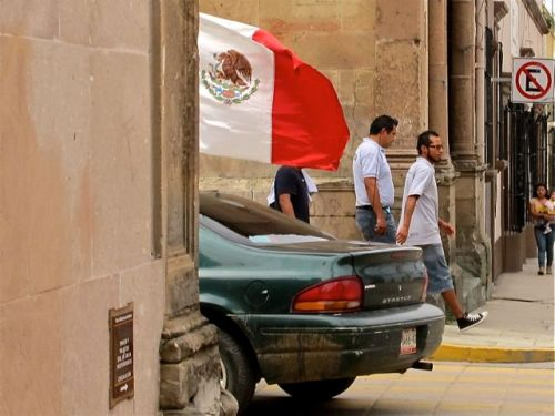 2/3rds of Mexican flag seen on car as it rounds a corner