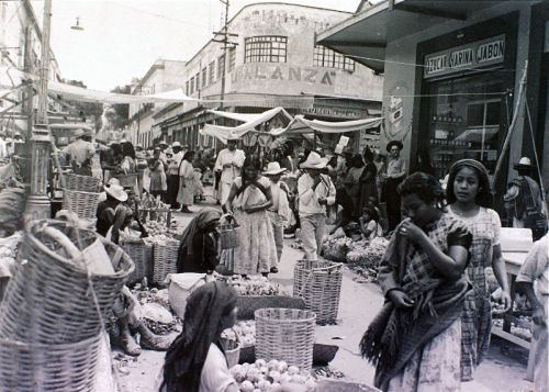 Black and white street scene of large baskets and indigenous vendors and shoppers.