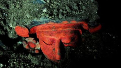Red urn shaped like a human face.