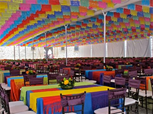 Interior of large tent decorated with multicolor tableclothes and papel picado on ceiling