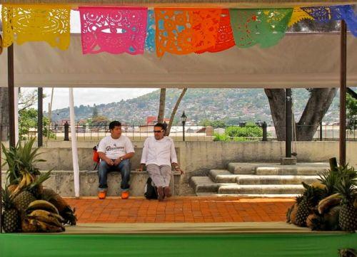 2 chefs sitting behind brick platform