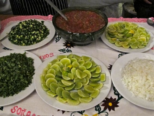 A bowl of a stew surrounded by platters of limes, rice, cilantro, and onions.