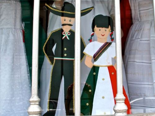 Boy and girl figures, seen through window bars in shop display dressed in traditional revolutionary clothing