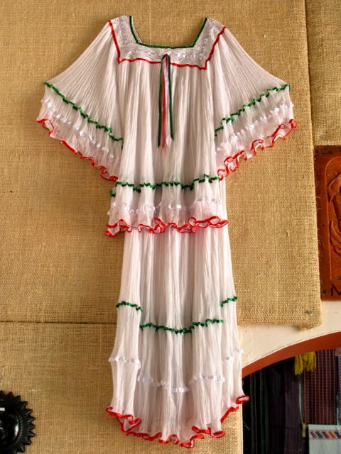White blouse and skirt with green and red trim.