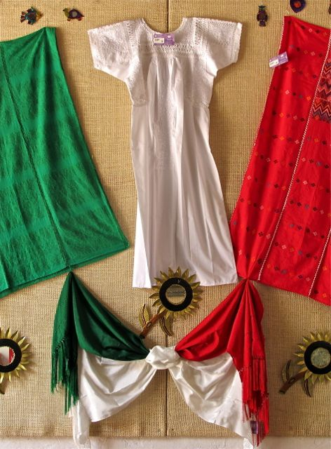 Green, white, and red dresses and shawls hanging on wall.