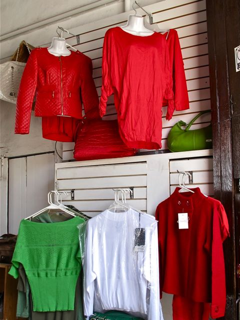 Green, white, and red sweaters hanging on display hooks.