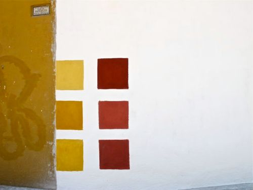 6 squares of paint swatches (putty to mustard to cinnamon) on white building.