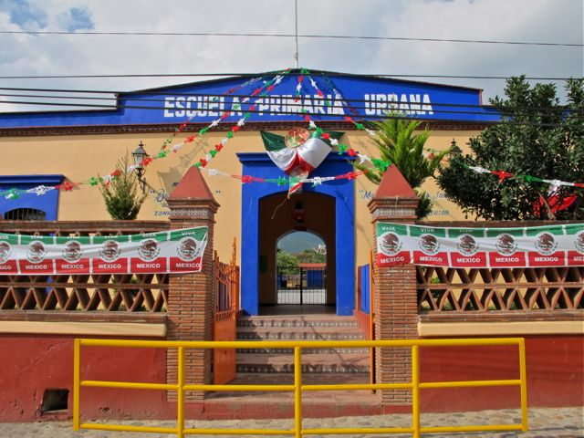 Blue and peach colored school decorated with Mexican flag banners and drapes