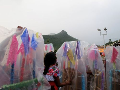 Cloudy sky; young girl surrounded by plastic covered canastas; Cerro Picacho in background.