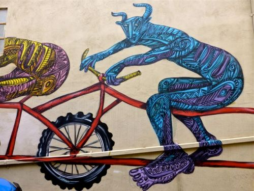 Painted horned creature riding a bike.