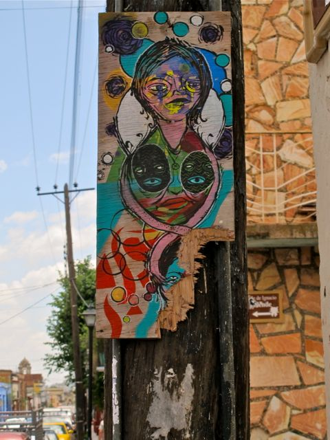 Colorful painting of faces tacked on telephone pole