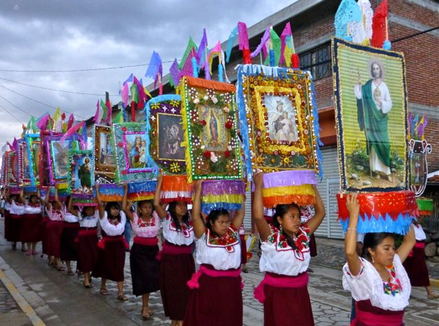 Young women wearing dark red wool wrap skirts and embroidered white blouses, carry large canastas on their heads