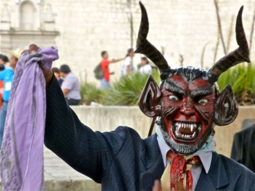 Man wearing a devil mask and holding a lavender colored bandana.