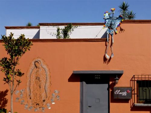 Skeleton perched on rooftop above a stencil of the Virgen of Guadalupe