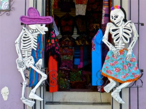 Male calavera and female calavera facing each other in a doorway