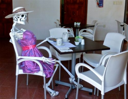 Catrina in lavender dress sitting at table