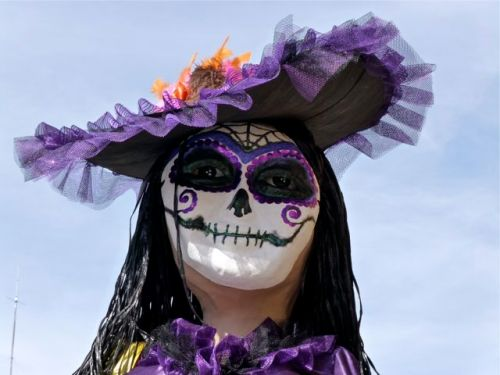 Close-up of face of a Catrina with lavender hat