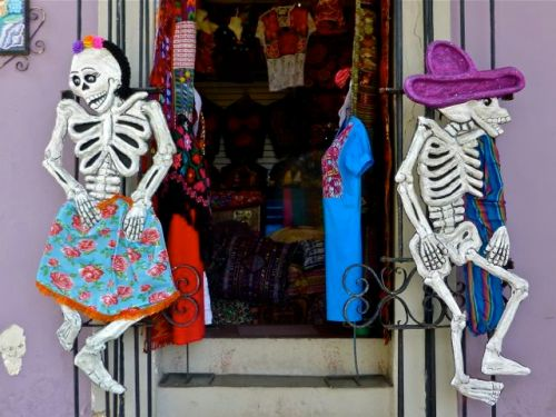 Male calavera and female calavera facing away from each other in a doorway