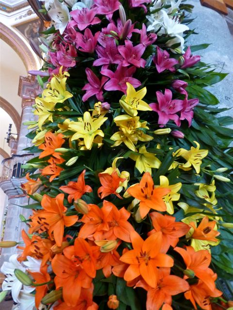 Close-up of orange, yellow, and lavender lilies covering a pillar